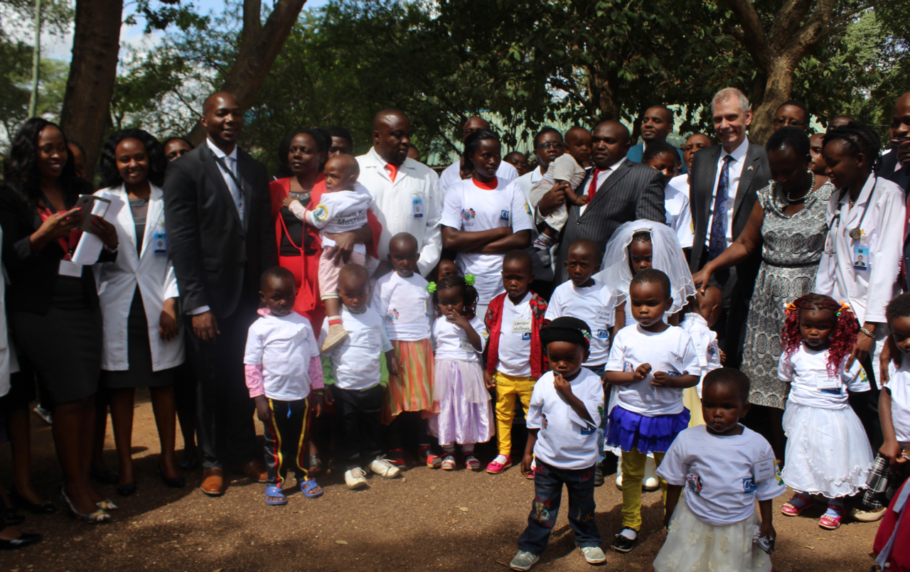 Ambassador Robert Godec and CHS CEO Dr Paul Wekesa, pose for a photo with the HEI graduands, implementing partners and county staff