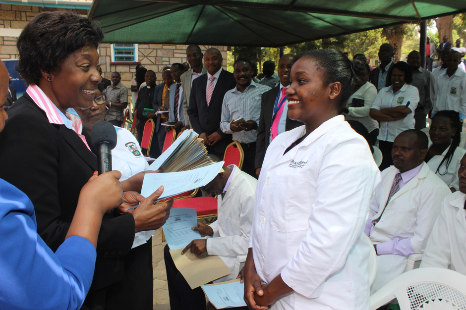 The Governor of Kitui County H.E. Charity Ngilu handing an appointment letter to one of the newly deployed health care workers